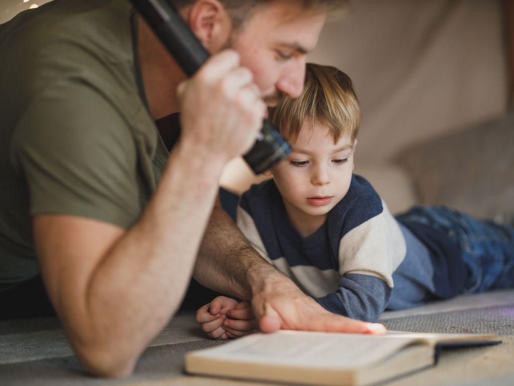 طفل ووالده، وقد بدأ رحل القراءة للطفل.