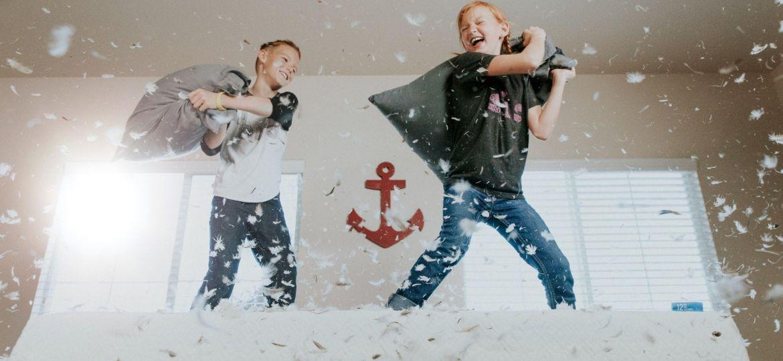 طفلان يلعبان بالوسائد ويقفزان؛ وقد يكون القفز الكثير من علامات فرط الحركة