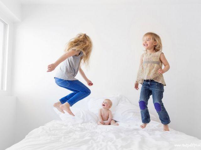 طفلتان تقفزان فوق سرير ومعهما رضيع يضحك.