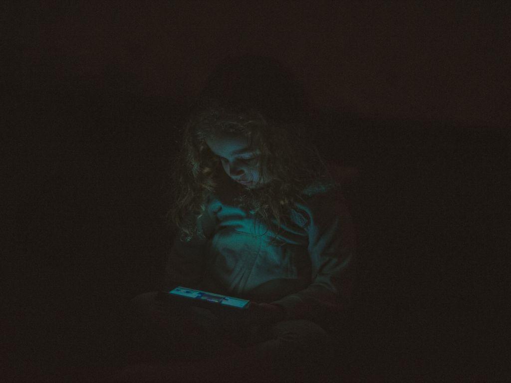 طفلة تستخدم جهاز إلكتروني في ظلام، ربما تعاني من إدمان الشاشات.