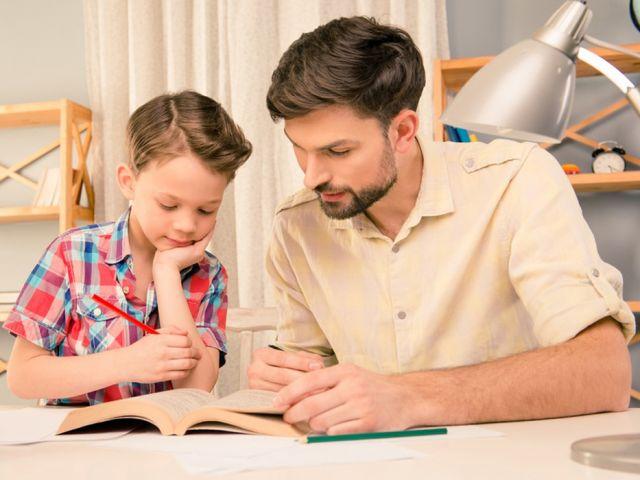 والد يقرأ مع طفله كتابًا.