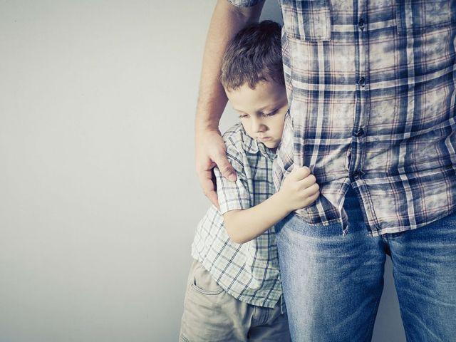 طفل يمسك بوالده وتبدو عليه علامات الخجل