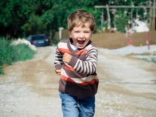 طفل في مرحلة الطفولة المتوسطة يركض فرحًا.